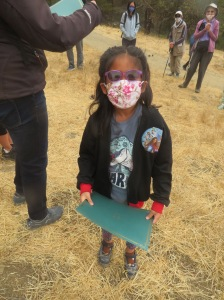 A little girl wearing a mask stands in a field with adults around her